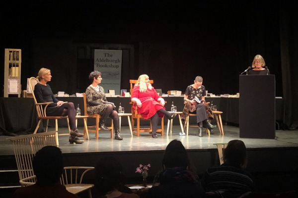Elizabeth Sennit-Clough, Jacqui Saphra, Amy Key and AK Blakemore sit onstage while Helen Taylor introduces