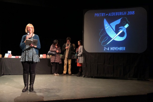Picture of Jean Sprackland reading on stage with the Poetry in Aldeburgh logo projected behind her