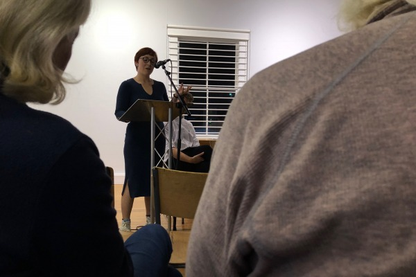 Ramona Herdman reads at a lectern in the Peter Pears Gallery